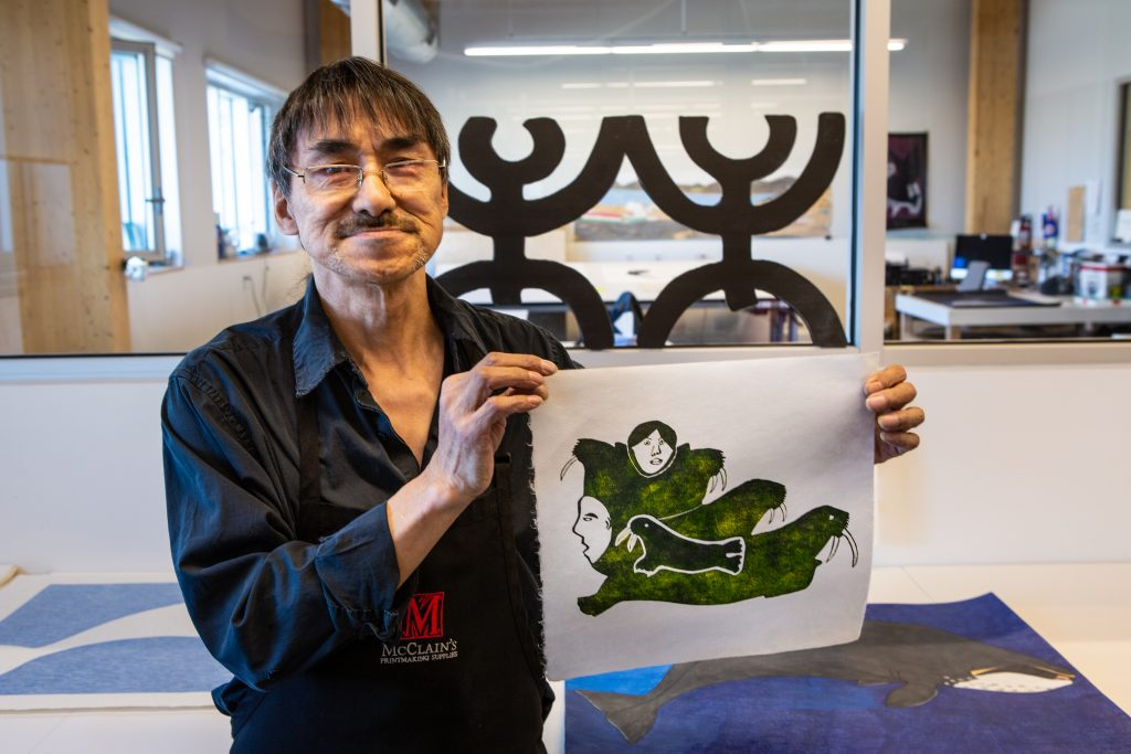 Inuit displaying a piece of their artwork