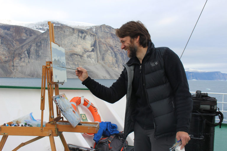Cory Trepanier painting in the Arctic. Photo by Beth Brown.