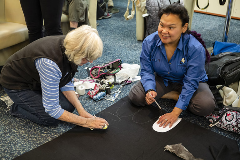 Alex showing guests how to create traditional Inuit clothing. Photo by Roger Pimenta