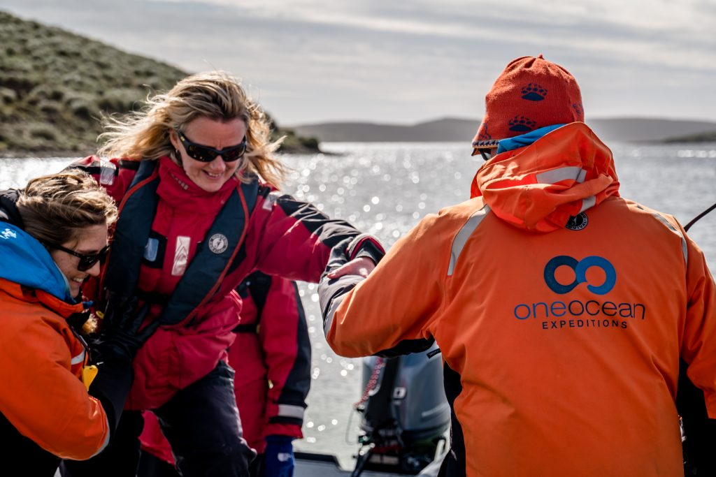 An expedition leader helping a passenger out of a zodiac.